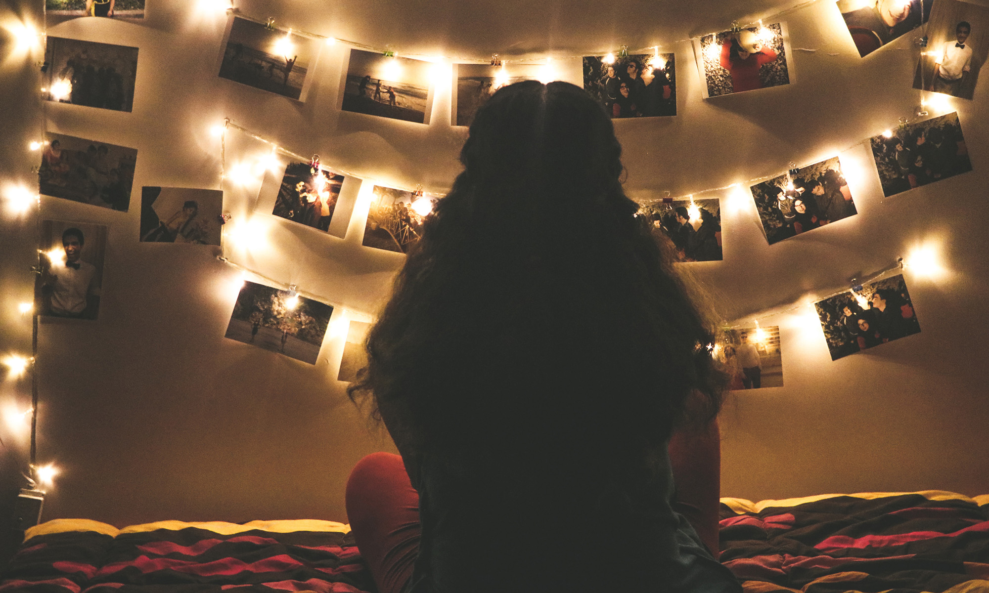Woman looking up photo display with lights in dimly lit room