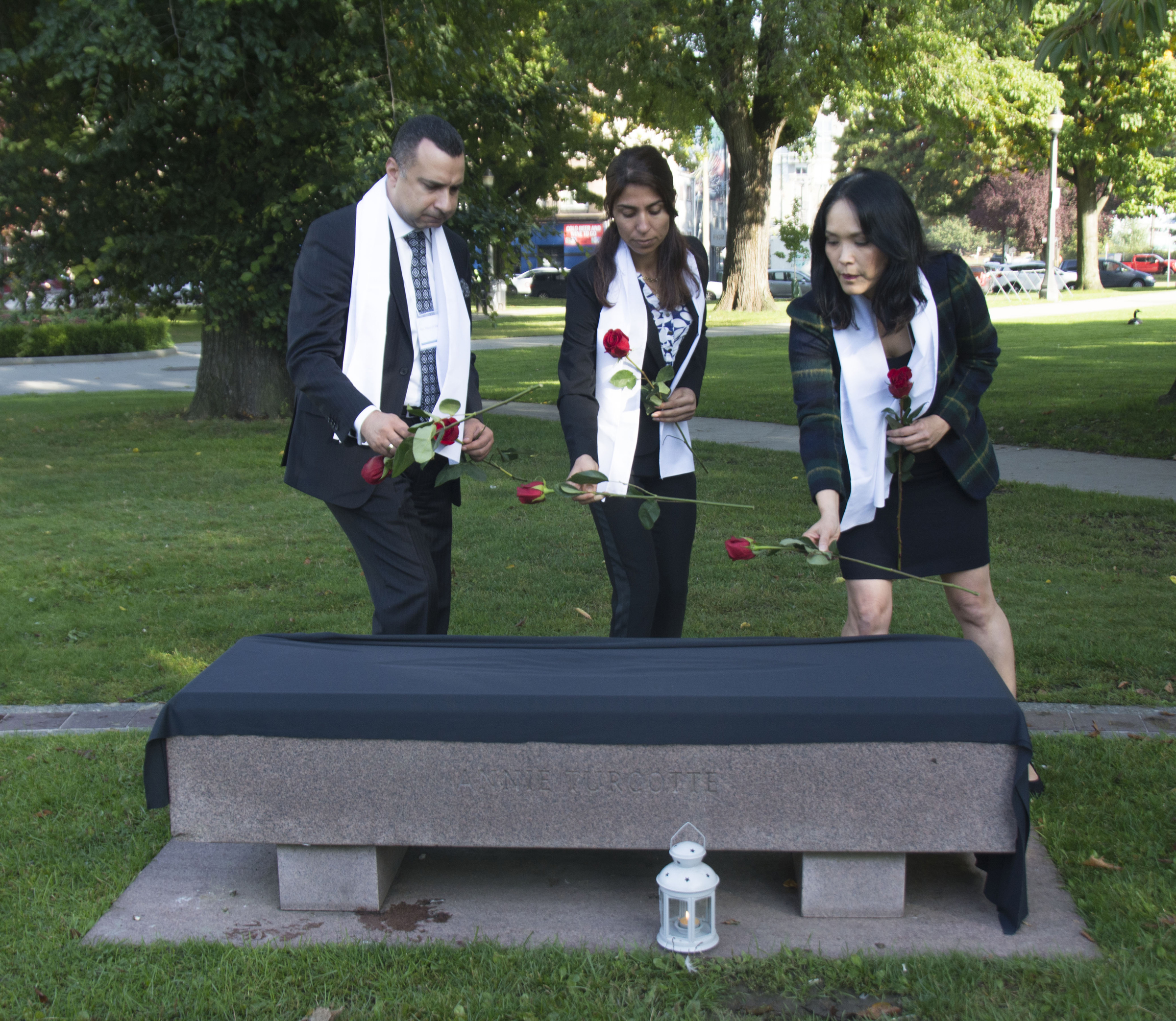 Placing roses on the veiled bench for Yazidi people who died in the genocide, starting August 3, 2014.Majed El Shafie of One Free World International with Adiba and MP Jenny Kwan (Vancouver East)